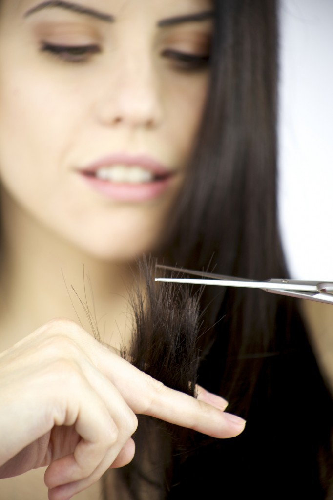 Closeup of scissor cutting hair with beautiful female looking